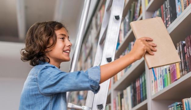 Мальчик кладет книгу на полку