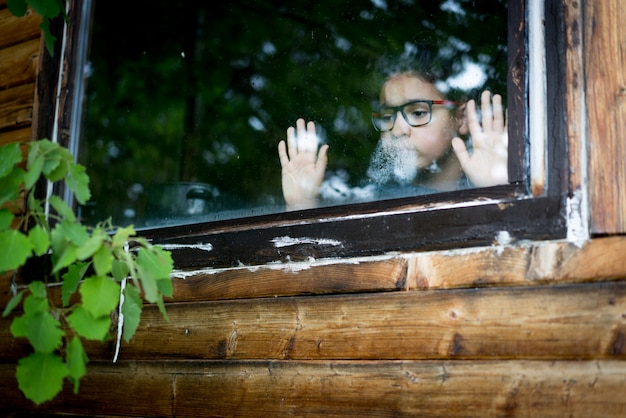 A boy putting his hand on a window and looking out