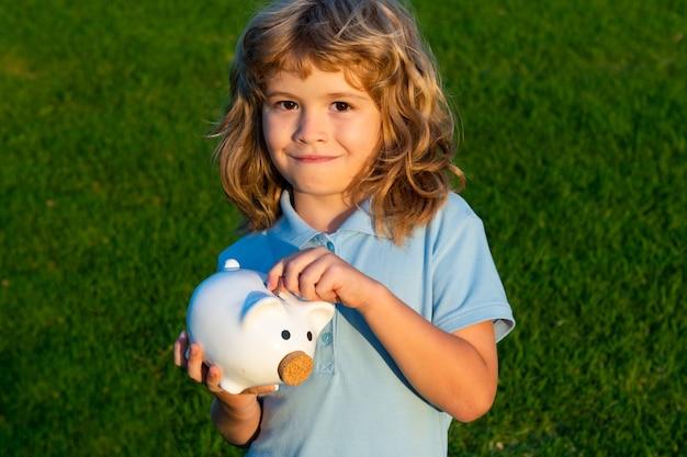 貯金箱にお金を入れる少年。貯金箱を保持しているうれしそうなかわいい小さな子供の肖像画。