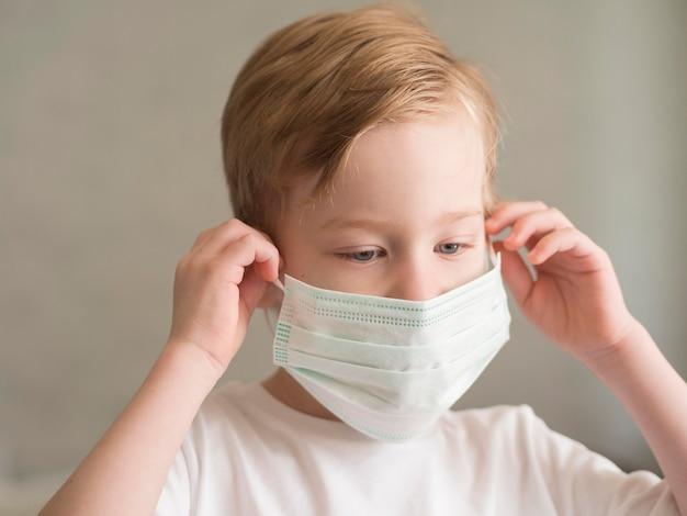 Мальчик надевает маску