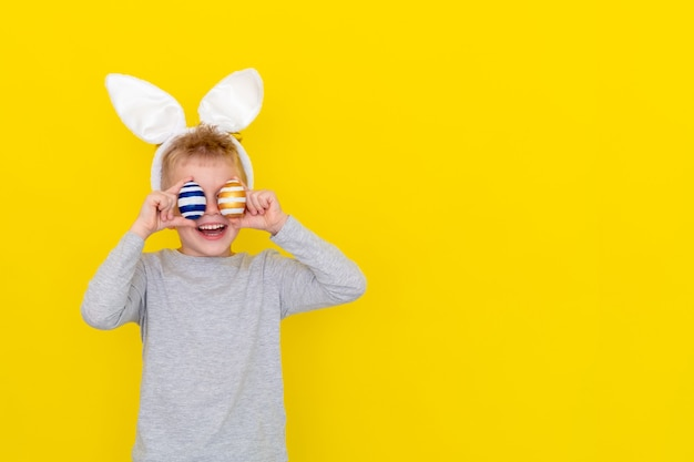 Boy in rabbit bunny ears on head with colored eggs on yellow