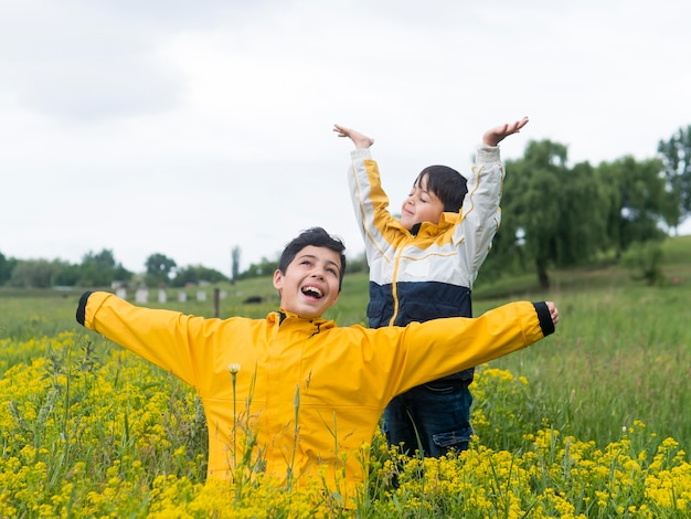 Boy in raincoat and his brother surrounded by flowers