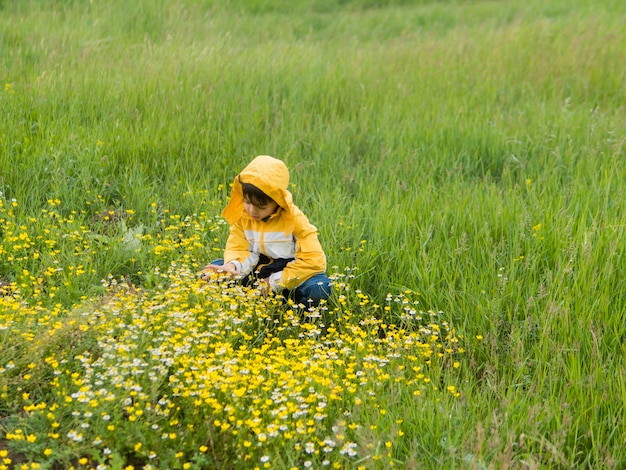 Boy in raincoat picking flowers long shot