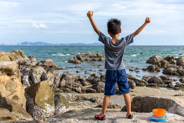 Boy raises his hands while standing on top rock looking at the sea.