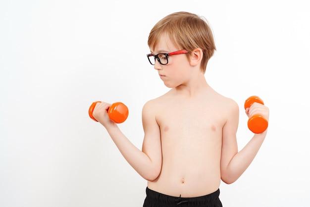 Мальчик поднимает гантель. тренировка милого ребенка с гантелями, изолированными на белизне. детский фитнес.