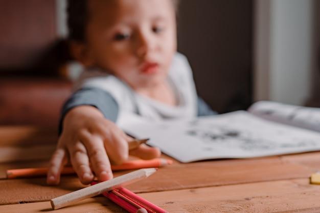 그림책을 칠하기 위해 색상에 도달하는 소년