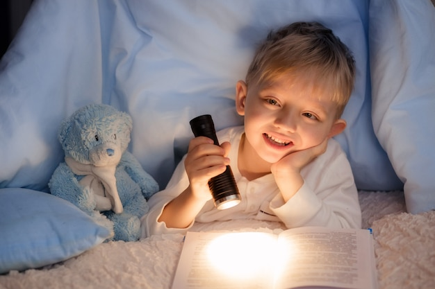 Boy reading a book under the covers with a toy bear