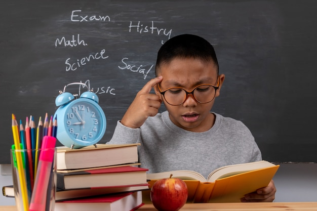 A boy reading books in classroom over chalkboard background.