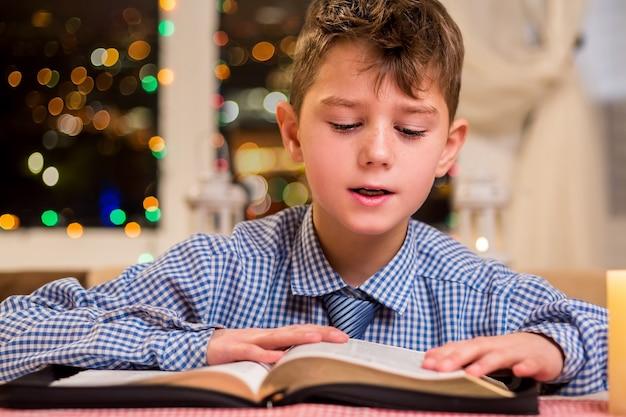 Мальчик читает толстую книгу. ребенок читает рядом с окном. чтение - хорошее хобби. интересная книга романов.