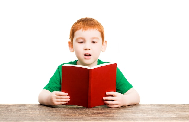 A boy reads the red book, a portrait of a child who learns on his own