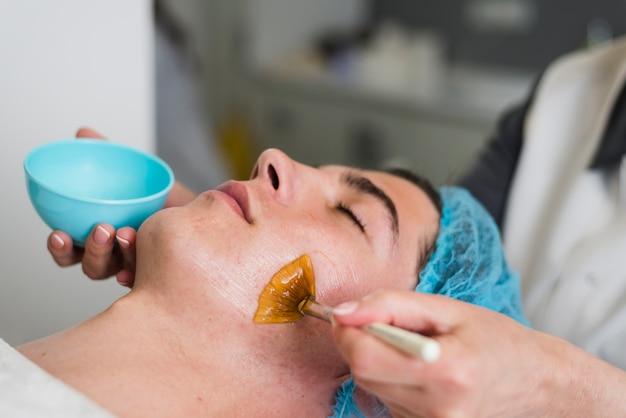 Boy receiving facial treatment in a beauty salon