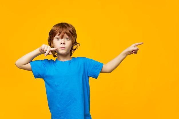 赤い髪の青いtシャツ黄色の孤立した背景のそばかすの少年とかわいい顔の側に指を向ける