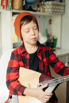 Boy in a red hat and a plaid shirt plays the balalaika. handsome boy holding his guitar. music lessons at home. hobby for the soul. home teaching music