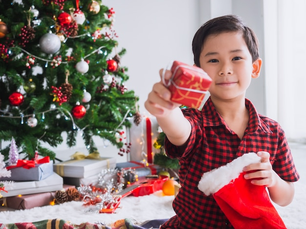 Boy in a red shirt is holding red sock and happy with funny to celebrate christmas with christmas tree