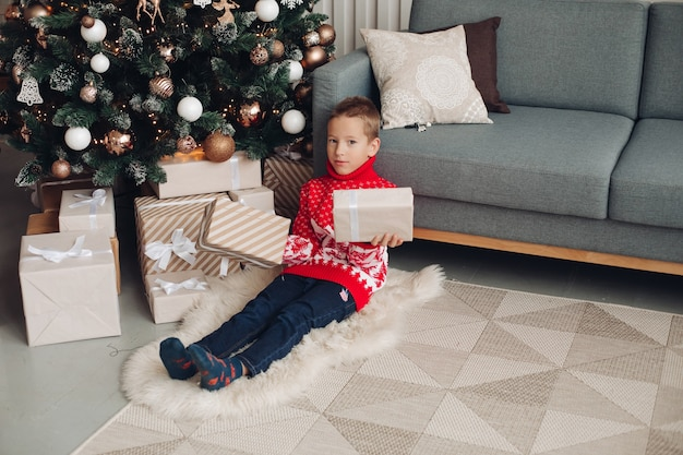 Boy in red winter sweater holding wrapped gifts under christmas tree