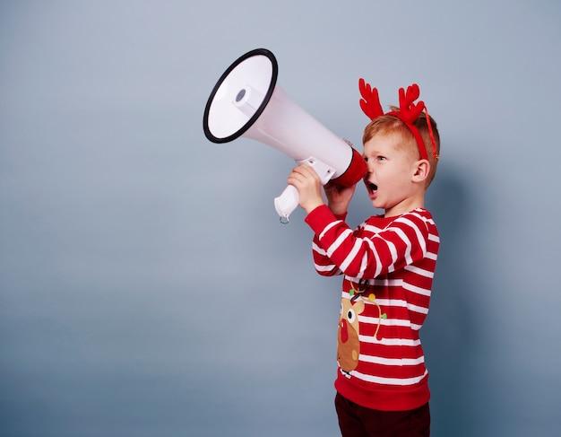 Ragazzo in costume da renna parlando nel megafono
