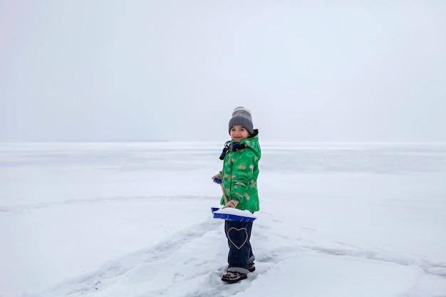 凍った湖の氷から雪を取り除く少年、冬、沈黙と野生の自然、ライフスタイル