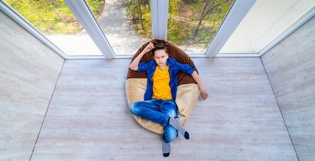 Мальчик отдыхает на балконе во время изоляции. карантин в домашних условиях для детей. мальчик расслабляется в мягком кресле.