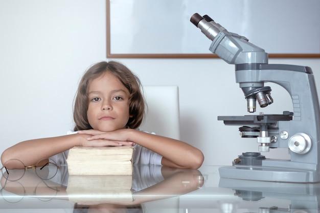 Мальчик отдыхает на книге, рядом с микроскопом
