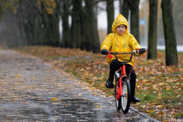 Мальчик едет на велосипеде в желтом плаще. мокрая аллея под дождем. осенний день