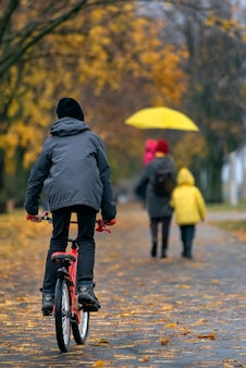 Boy rides bicycle in autumn park against the backdrop of passers-by. vertical frame.