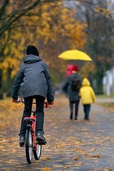 Мальчик катается на велосипеде в осеннем парке на фоне прохожих. вертикальная рамка.