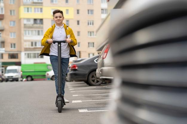 少年は通りを下って電動スクーターに乗る