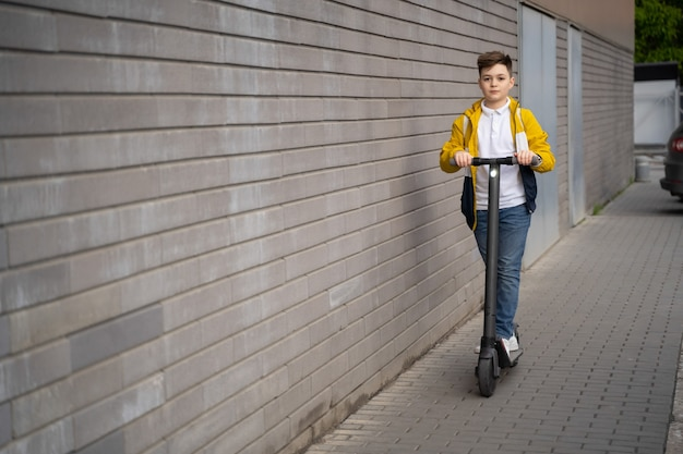 少年は街の通りを電動スクーターに乗る