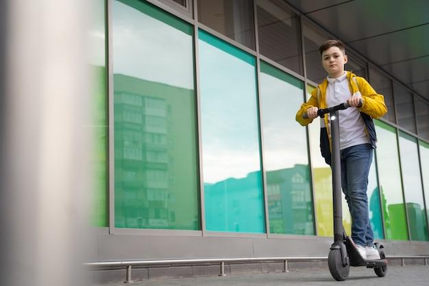 少年は電動スクーターに乗る