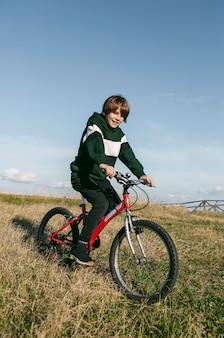 야외 잔디에 그의 자전거를 타는 소년