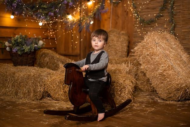 わらの束を持つファームでおもちゃの馬に乗る少年