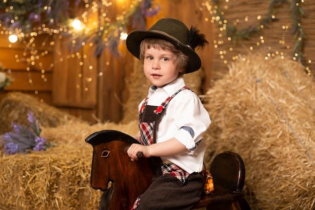 ファームでレトロな衣装を着ておもちゃの馬に乗る少年