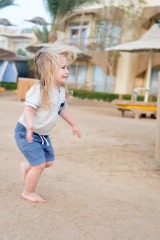 少年は裸足で砂の上を走ります。活動、エネルギー、レジャー。幸せな子供の頃のコンセプト。晴れた日に砂浜で金髪の子供が笑顔。夏休み、レクリエーション。