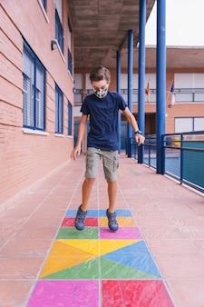 コビッドパンデミックの最中にフェイスマスクを持って校庭で走ったりジャンプしたりする少年。コビッドパンデミック中に学校に戻る