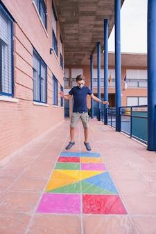 Covidパンデミックの最中にフェイスマスクを持って校庭で走ったりジャンプしたりする少年。