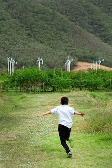 Boy running in field and wind turbines in backgroun