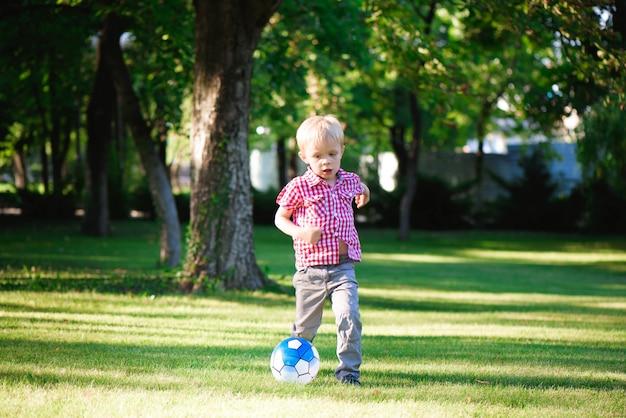 フィールド上のボールに向かって走っている少年