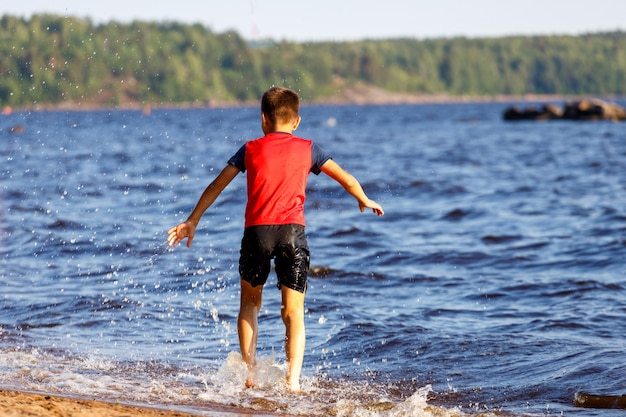 Boy runs and jumps on the shore of the lake. high quality photo