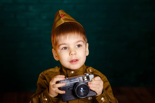 Boy in russian military uniform with camera. child war correspondent