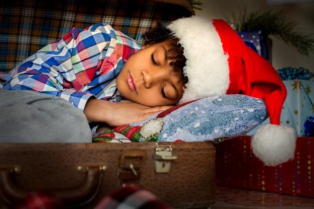 Рождественский сон мальчика рядом с подарками. афро-ребенок спит возле подарков. просыпайтесь и празднуйте. счастье тебя ждет.