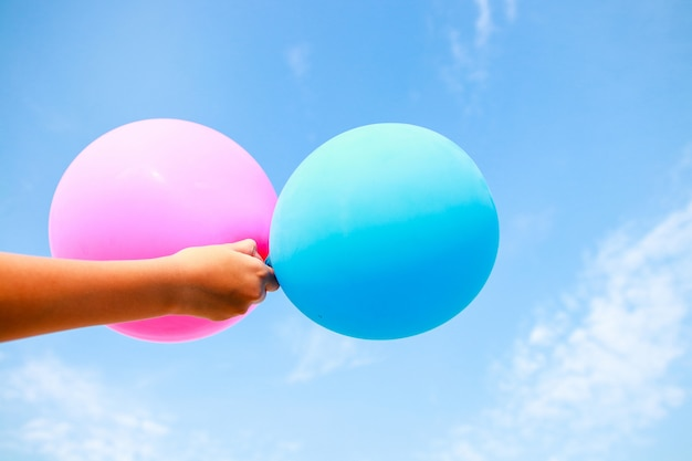 The boy's hand holds blue and pink balloons. the background is bright sky. happy