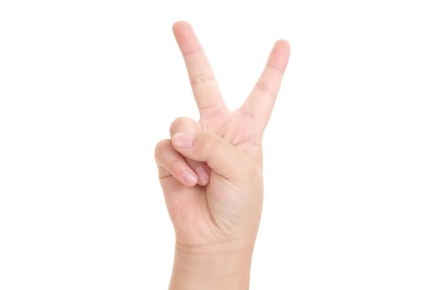 勝利の兆候と白い背景で隔離の平和のクローズアップを示す少年の手。