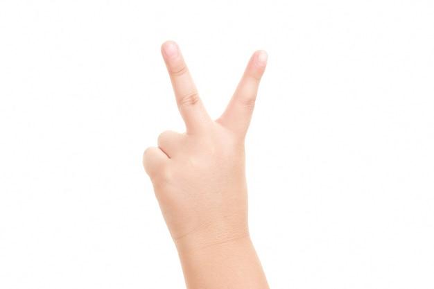 勝利と平和のクローズアップの兆候を示す少年の手