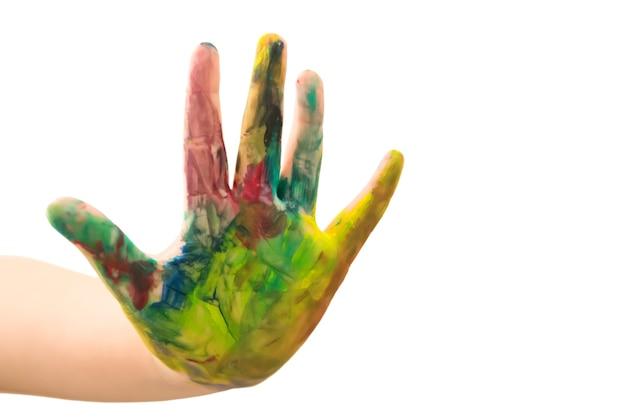흰색 배경에 분리된 여러 가지 빛깔의 페인트로 얼룩진 소년의 손. 아이는 다채로운 손 그림을 보여줍니다. 안녕하세요 파이브 제스처입니다.