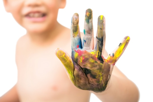 흰색 배경에 격리된 웃는 얼굴로 여러 가지 빛깔의 페인트로 얼룩진 소년의 손. 아이는 다채로운 손 그림을 보여줍니다. 안녕하세요 파이브 제스처입니다.