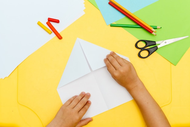소년의 손은 노란색 테이블에 종이 비행 비행기