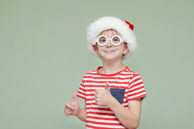 Boy in santa hat and glasses smiling and showing thumbs up. portrait