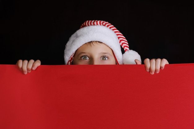 Boy in santa's hat holding the red blank banner for christmas greetings. isolated on black