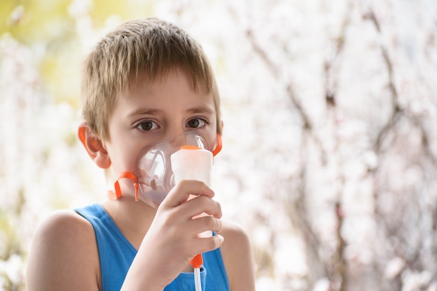 Boy of school age makes inhalation at home. prevention