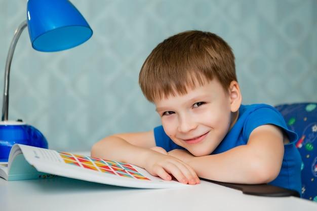 男の子の男子生徒がレッスンを教えている間机で眠りに落ちる